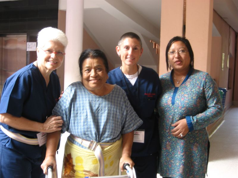 Volunteers pose for a picture with a patient after a rehabilitation session.